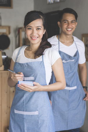 Happy attractive asian female waiter in apron writing order and looking at camera. her partner at the background
