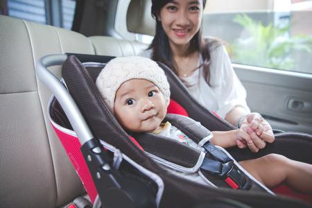 asiento coche: Retrato de una madre asegurando su bebé en el asiento de seguridad en su coche