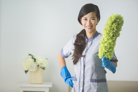 bioclean: cleaner maid woman with duster and uniform cleaning living room at home