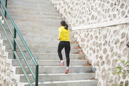 stairs: A portrait of a Young asian woman exercising outdoor in yellow jacket, jogging going up and down the stair Stock Photo