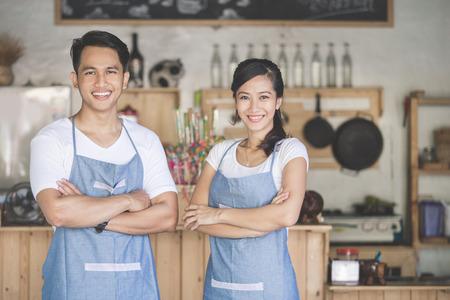 mandil: exitoso dueño de la pequeña empresa orgullosamente de pie en frente de su café