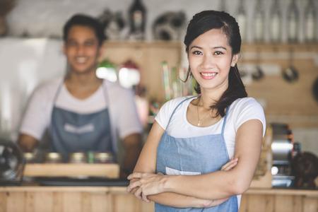 meseros: propietario de la pequeña empresa exitosa de pie con los brazos cruzados con la pareja en el fondo