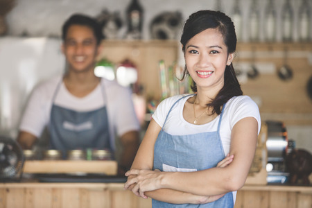bars: Successful small business owner standing with crossed arms with partner at the background Stock Photo
