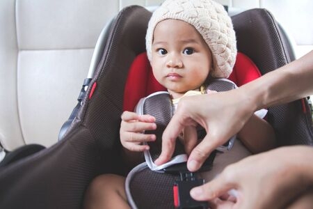 child seat: portrait of a Mother securing her baby in the car seat in her car
