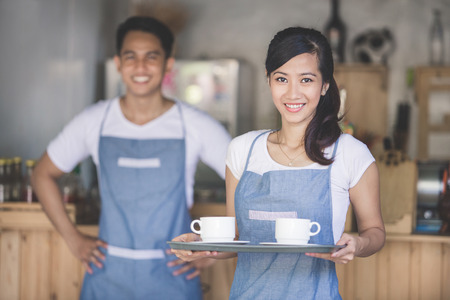 Waitress holding tray with cappuccinos at the coffee shop Stock Photo