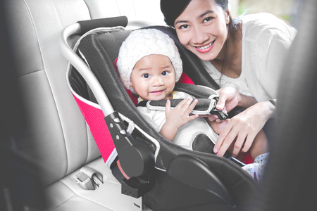 securing: portrait of a Mother securing her baby in the car seat in her car. smiling to camera