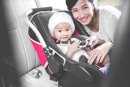 asiento: Retrato de una madre asegurando su bebé en el asiento de seguridad en su coche. sonriendo a la cámara