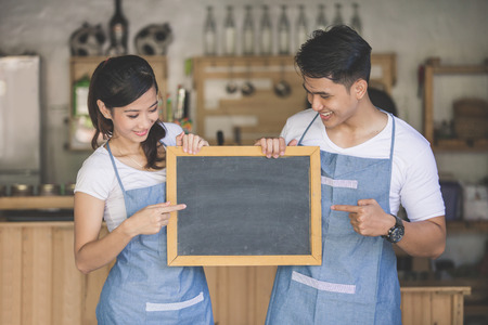 portrait of two young business partner open their coffe shop. standing with blank blackboard sign