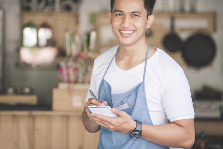 young guy: Happy asian male waiter in apron writing order and looking at camera