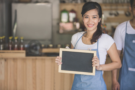 open business: happy small business owner ready to open her cafe for the first time. holding white board Stock Photo