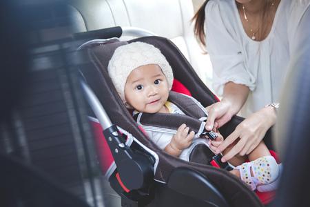 Retrato de una madre asegurando su bebé en el asiento de seguridad en su coche Foto de archivo - 54111464