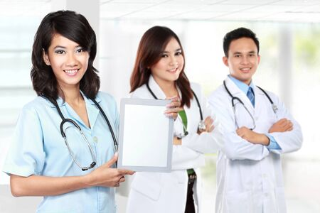 asian group: medical worker doctor showing tablet pc. partner at the background Stock Photo