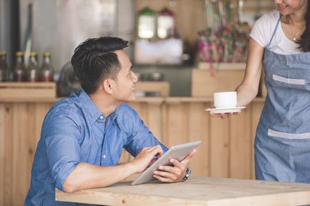 negocios comida: Retrato de hombre joven sentado en una cafetería que sirve café, mientras que la camarera le