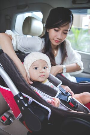 securing: portrait of a Mother securing her baby in the car seat in her car