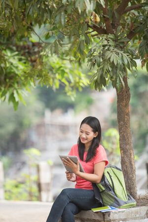 A portrait of a young Asian student sitting outdoor using tablet pc