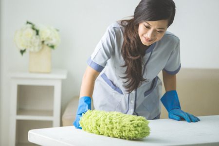 cleaner maid woman with duster and uniform cleaning table in living room at home Foto de archivo