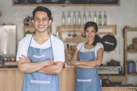 propietario de la pequeña empresa exitosa de pie con los brazos cruzados con la pareja en el fondo