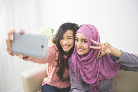 indonesian girl: two happy young muslim woman take self portrait with handphone at home Stock Photo
