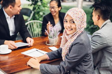 Attractive affaires asiatique souriant à la caméra lors d'une réunion d'affaires