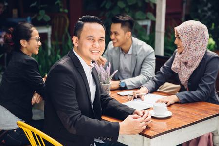 bel homme d'affaires souriant à la caméra lors d'une réunion d'affaires
