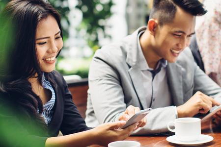 Zakenmensen die smartphone-gadgets gebruiken, terwijl ze koffie drinken Stockfoto