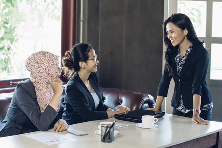 break from work: portrait of three asian woman talking while sitting on a couch at the office