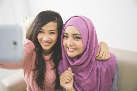 two happy young muslim woman take self portrait with handphone at home Stockfoto