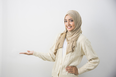 Ritratto di una giovane donna musulmana che mostra un'area vuota per segno o copyspace