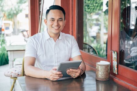 millennial: portrait of Young successful businessman with tablet in cafe Stock Photo