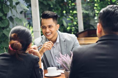 自信を持って実業家カフェで彼のチームとの会議の率直な肖像画