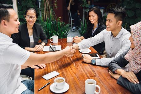 Porträt von Geschäftsleute Händeschütteln während einer Mittagspause im Café