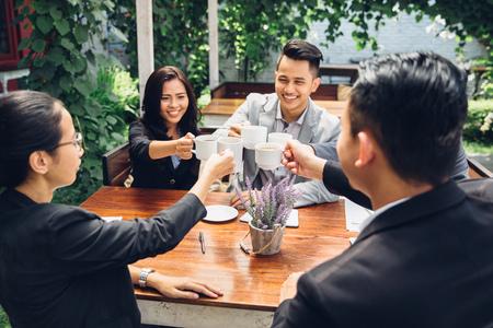 カフェで幸せなアジア ビジネス コーヒーとお友達を応援 写真素材