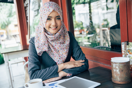 muslim: Young businesswoman on a coffee break at cafe