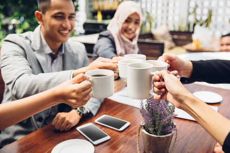 muslim: happy asian business Friends Cheering With Coffee at cafe