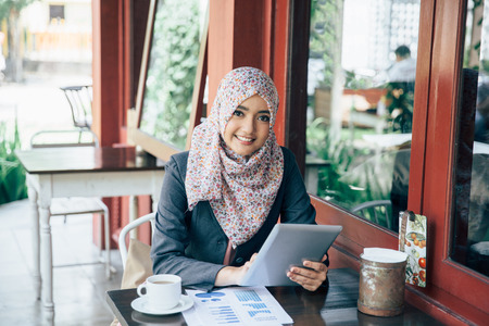 Young businesswoman on a coffee break. Using tablet computer Stock Photo
