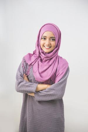 頭の中若いアジアのイスラム教徒の女性が腕を組んで笑顔をスカーフします。 写真素材
