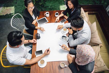 personas leyendo: Retrato de hombre de negocios y de negocios sentado en la reunión de café discutiendo algo sobre el papel. disparar desde la vista superior