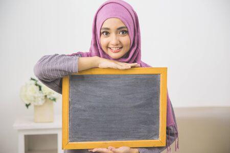 executive women: portrait of woman wearing scarf showing blank board Stock Photo