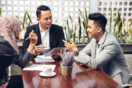 jovenes empresarios: las personas y la tecnología de negocios concepto de trabajo en equipo - hombre de negocios sonriente y mujeres de negocios con ordenador que cumpla Tablet PC en la cafetería Foto de archivo