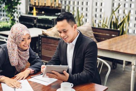 Dwa azjatyckie spotkanie biznesowe w kawiarni przy u? Yciu komputera typu tablet