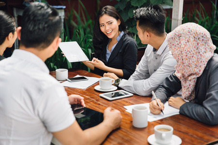 portrait of young asian business people meeting in a cafe