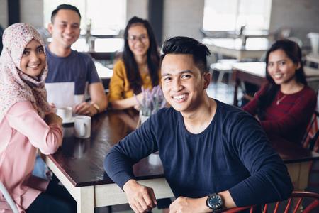 portret van vrienden plezier samen in een cafe. kijken naar de camera