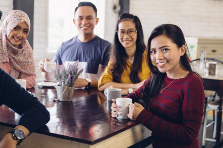 asian group: portrait of friends having fun together in a cafe. looking at camera Stock Photo