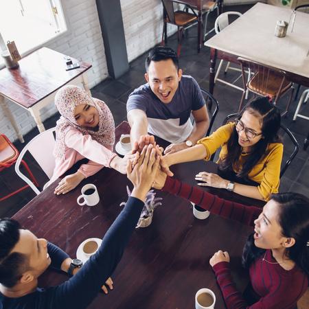 almuerzo: retrato de un amigo asiático dando de alta cinco en el café