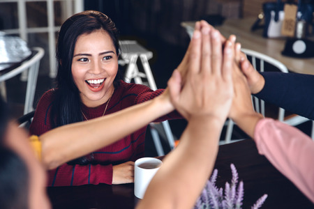 excited people: portrait of young enthusiastic team giving high five Stock Photo