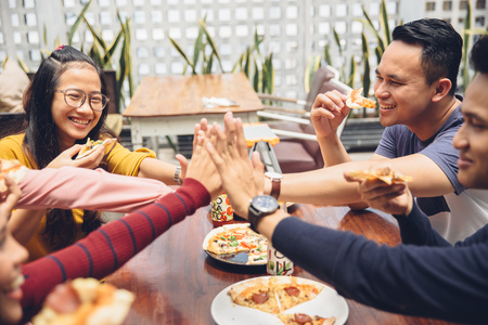 retrato de un amigo asiático dando de alta cinco en el café mientras que tener un almuerzo Foto de archivo