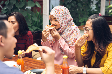 Muslim: Group Of Young Friends Enjoying Meal In Outdoor Restaurant