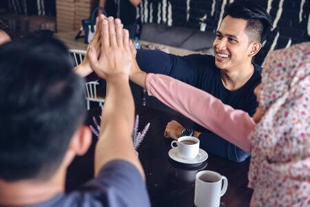 Happy young friends giving a high five congratulations as they sit together in a cafeteria enjoying a cup of hot coffee 写真素材