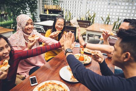 amicizia: ritratto di amico asiatico dando il cinque al caff�, pur avendo un pranzo