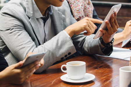 break from work: business people using smartphone gadget while having a coffee break at cafe